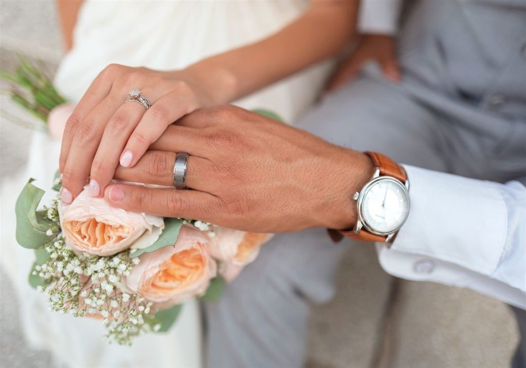 A couples hands showing their wedding rings